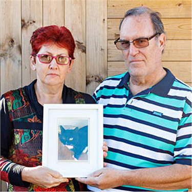 Couple holding a picture of a cat
