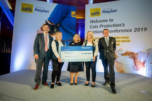 Two men and three women holding large cheque at Cats Protection conference