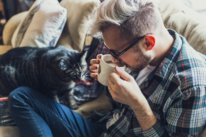 man on sofa drinking coffee with cat