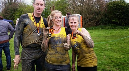 two women and one man in muddy Cats Protection vests