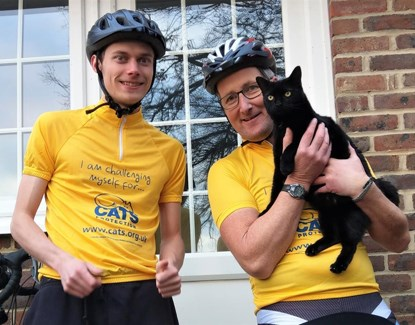 Cyclists in Cats Protection tops holding black cat