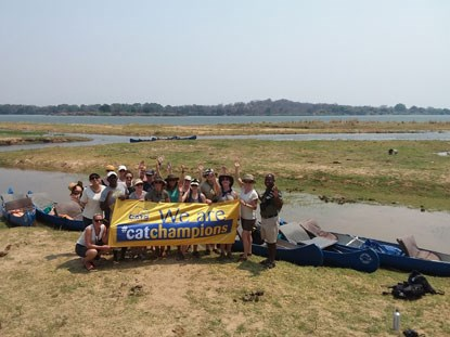 group of people next to  river holding a Cat Champions Cats Protection banner