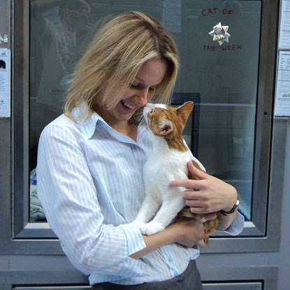 blonde woman holding ginger and white cat while they rub noses