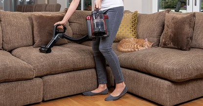 woman hoovering sofa that ginger tabby cat is asleep on