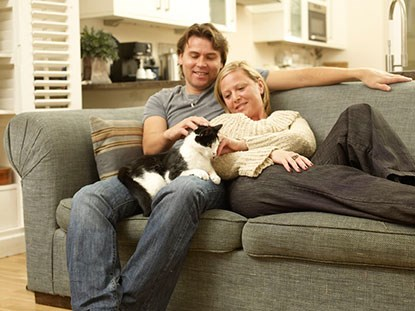 man and woman on sofa with black and white cat