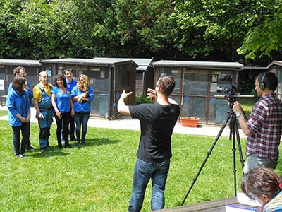 film crew directing Cats Protection staff and volunteers in garden