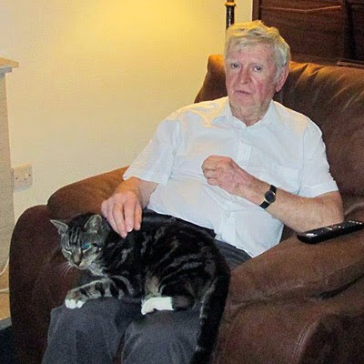 older man sitting with tabby cat on his lap