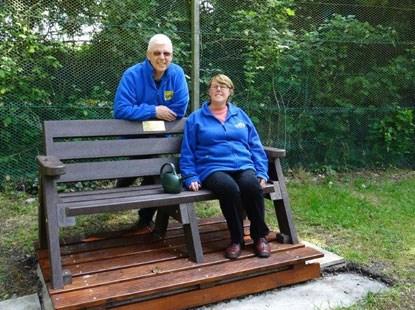 gardening volunteers by a bench in Cats Protection garden