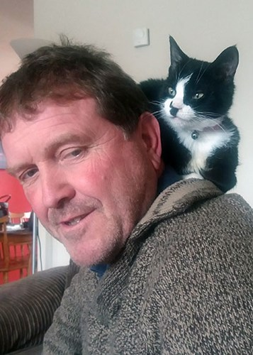 black and white cat sitting on man's shoulder