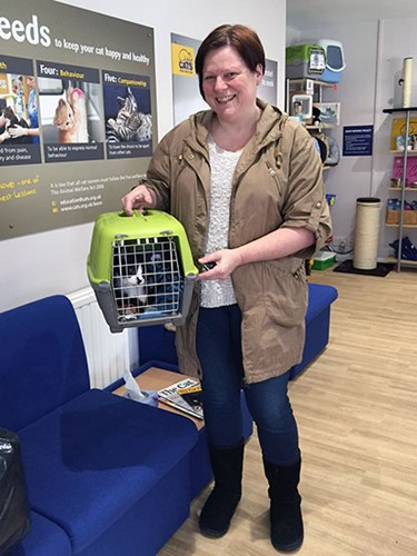 woman holding black and white cat in carrier in Cats Protection centre