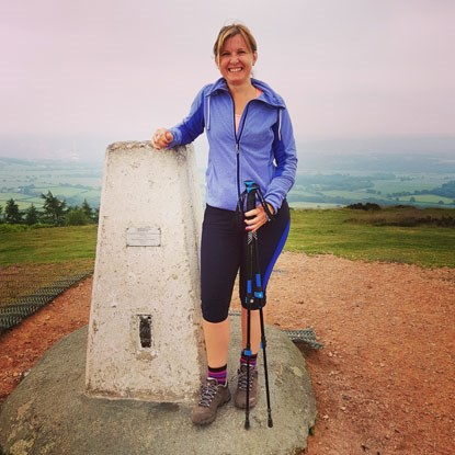 woman standing at the top of the Wrekin in Shopshire in trekking gear
