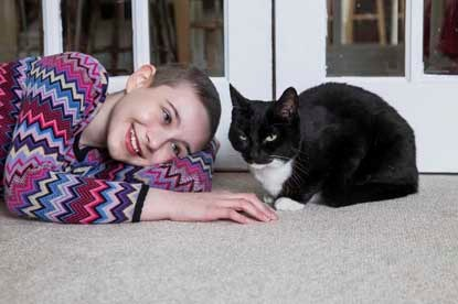 young girl lying on floor with a black and white cat