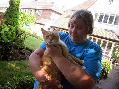 tearful woman holding ginger cat in garden