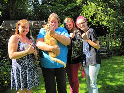 Ginger cat held by tearful woman in a garden