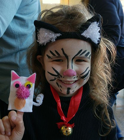 young girl with face painted as a cat