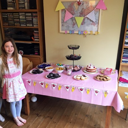 girl standing next to table full of afternoon tea, cakes and biscuits