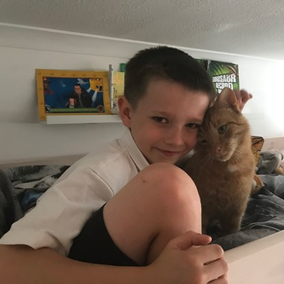 young boy hugging ginger cat
