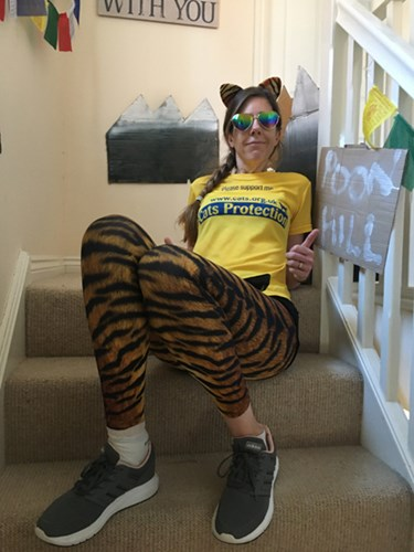 woman in Cats Protection t-shirt and fitness gear sitting on the stairs