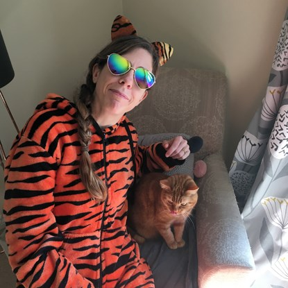 woman in tiger onesie with a ginger cat