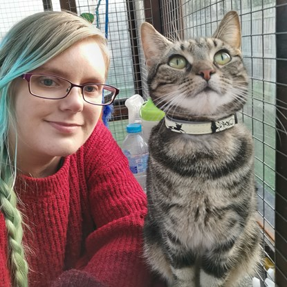 blonde woman next to tabby cat with collar