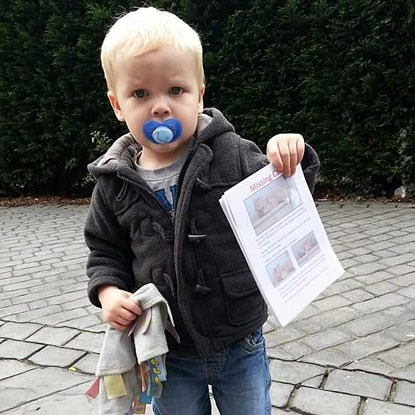 blonde toddler holding missing cat posters