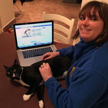 lady in Cats Protection fleece on laptop with black cat