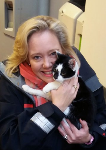 blonde lady hugging black and white cat