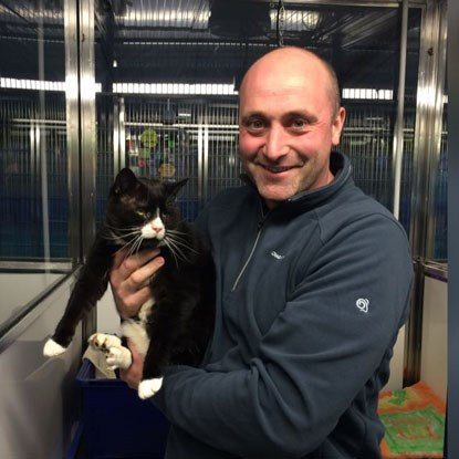 man in animal shelter holding black cat