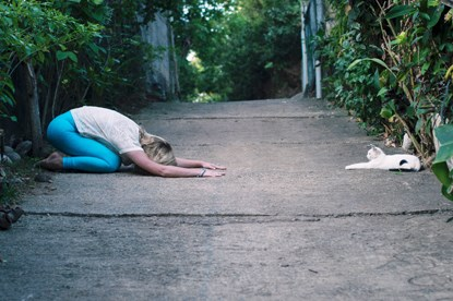 woman and cat doing yoga pose outside