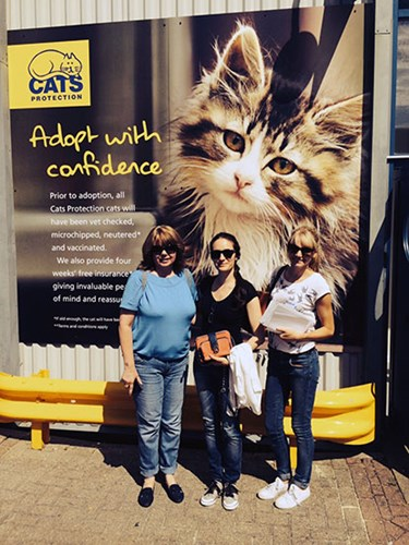 three women in front of Cats Protection banner