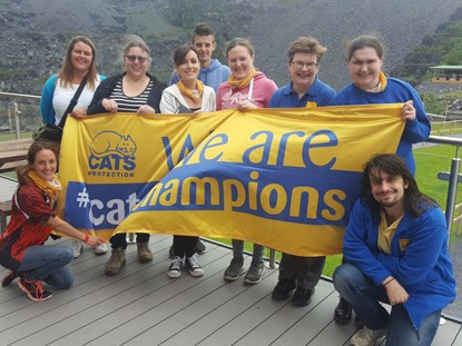 group of people holding Cats Protection Cat Champions banner