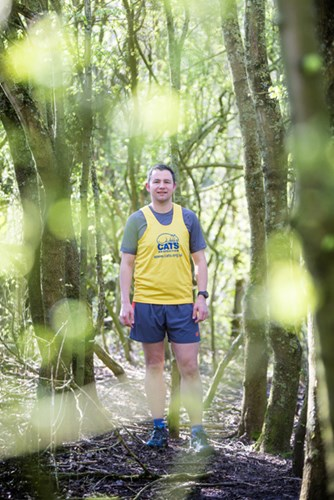 man standing in woods wearing Cats Protection running vest