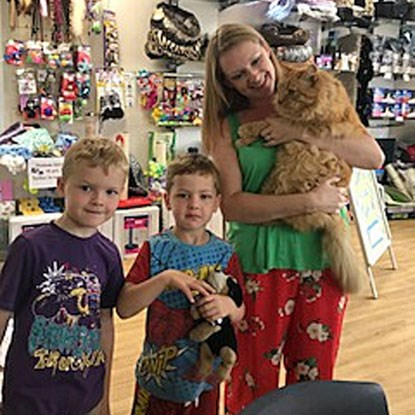 blonde woman and children with ginger cat in Cats Protection shop