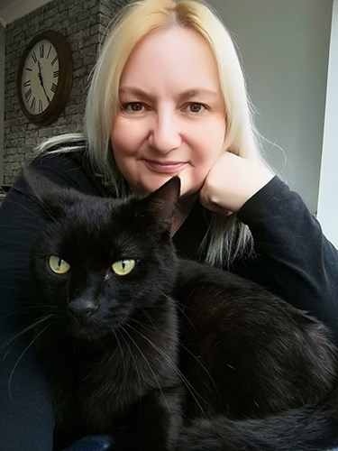 blonde woman with black cat on her lap