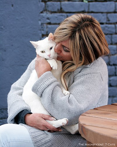 blonde woman hugging white cat