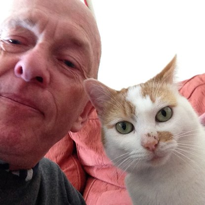 selfie of a man and his white and ginger cat