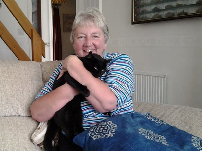 woman cuddling black cat on sofa
