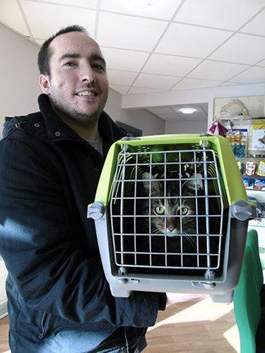 man holding cat carrier containing tabby cat