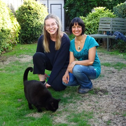 two women in garden with black cat