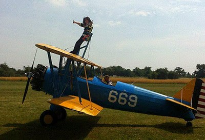 woman wing walking on top of biplane