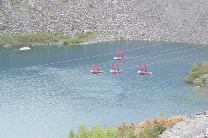 four people doing a zipwire challenge over a lake