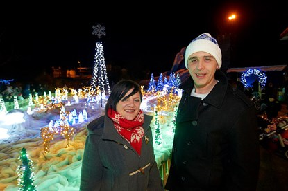 man and woman standing in front of big Christmas light display