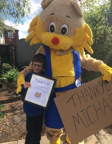 Persona in costume da mascotte di gatto con un braccio intorno a un giovane ragazzo bruno dai capelli corti che tiene in mano un certificato di ringraziamento thank