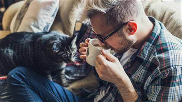 man with glasses drinking coffee in starbucks mug with tabby cat